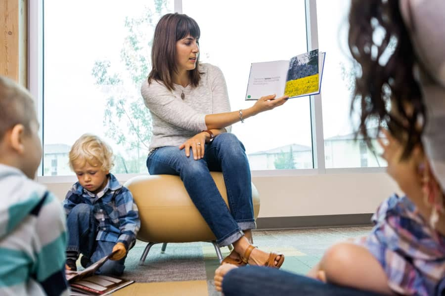 teacher reading books at field trip to library for toddlers