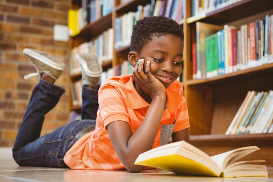 student reading a book to meet a reading goal to qualify for field trip near him